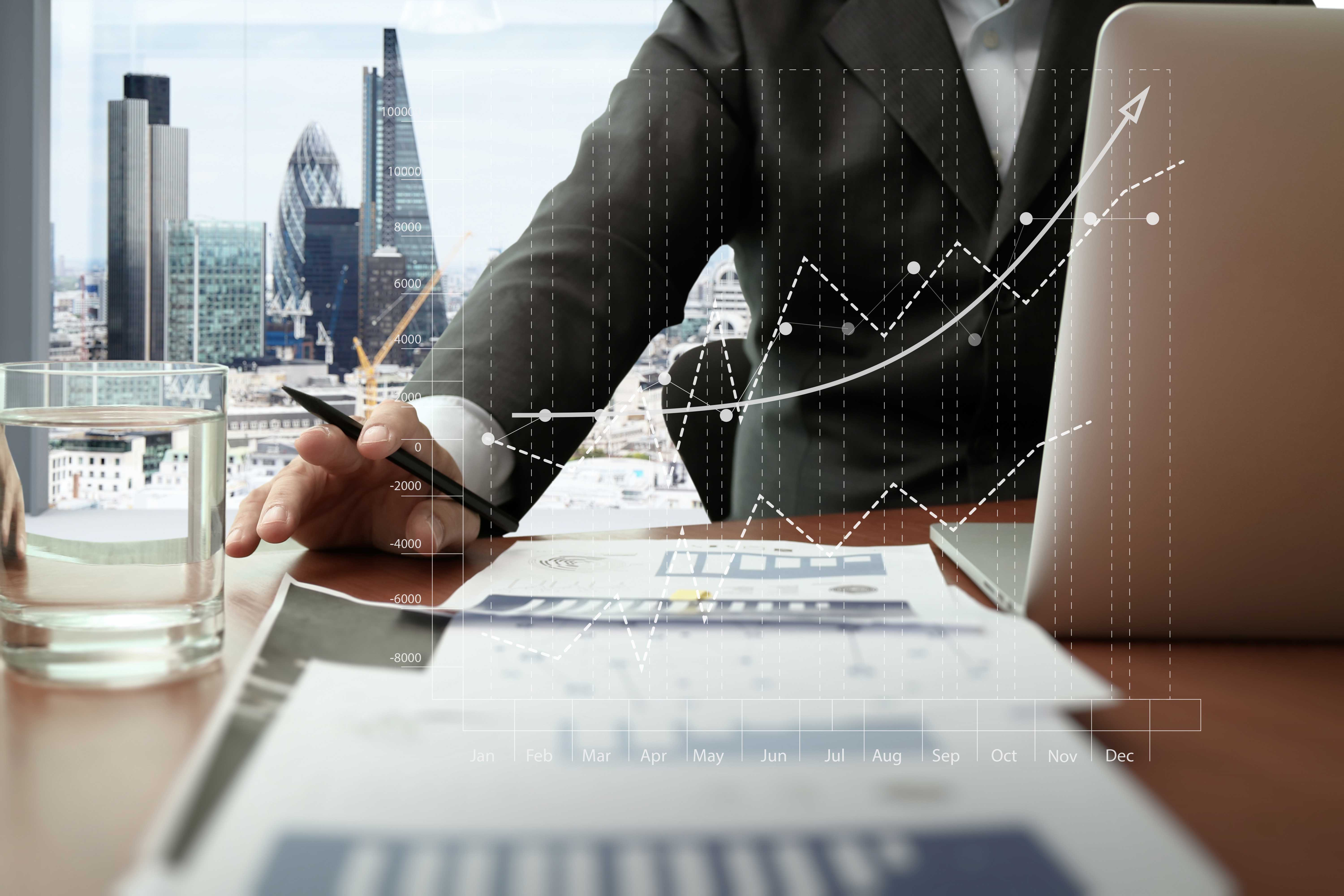 business documents on office table with smart phone and digital tablet and graph business diagram and man working in the background with London city view